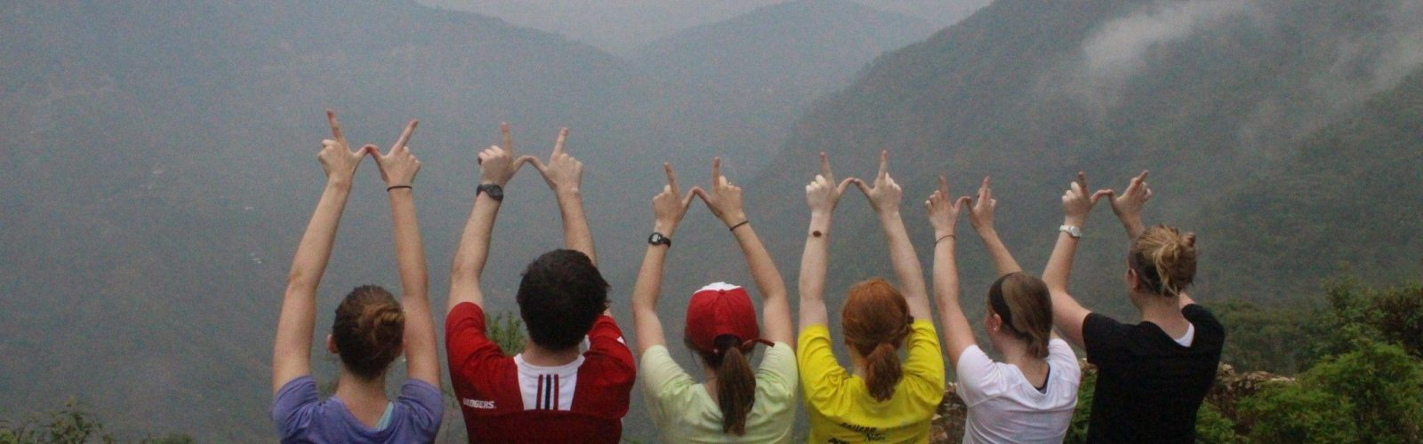 Students have their arms raised, making a W with their hands, looking out at mountains in the mist.