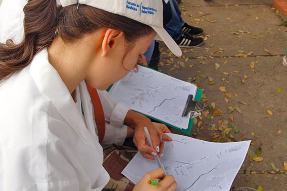 A student in a white coat works on a map in her lap during a field course in Thailand.